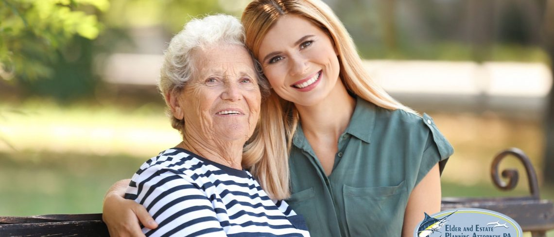 Young woman holding elder woman on park bench